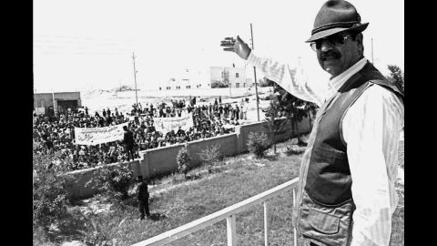 President Saddam Hussein waves to supporters from the balcony of the mayor's office in Mosul on a trip to see how farmers were faring under international sanctions.