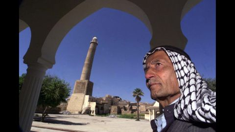 """In this 2001 photo, a man stands before the Great Mosque's minaret, which leans like the Tower of Pisa and is nicknamed """"al-Habda,"""" or """"the hunchback."""""""