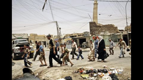 Moslawis walk past trash strewn about a busy market area in Mosul in 2009.