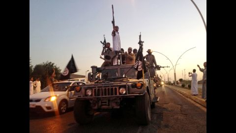 ISIS fighters parade down a main road in a commandeered Iraqi security forces vehicle after the militant group took control of Mosul in June 2014.