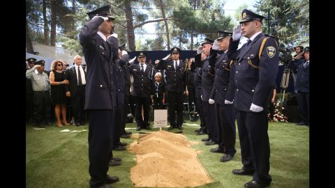 Members of the Knesset Guard salute around the grave.