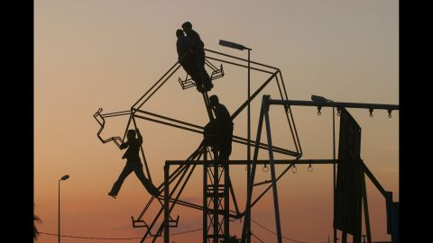Kurdish children play on a broken ferris wheel in Mosul, a month before the invasion of Iraq in 2003.