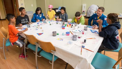 Astronauts Reid Wiseman and Stott joined patients to paint the Unity flight suit. To the immediate left of Wiseman sits Jacob Ballard, a patient who battled Ewing's sarcoma at MD Anderson.
