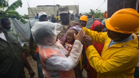 Nice Simon, the mayor of Tabarre, Haiti, holds a baby as she helps evacuate the area along a river.