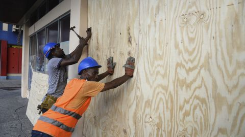 A worker nails a board to a storefront window in Kingston on Saturday, October 1.