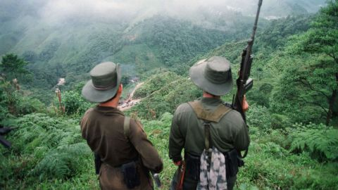 """FLORENCIA, COLOMBIA:  Two armed soldiers belonging to the Revolutionry Armed Forces of Colombia (FARC) monitor the Berlin pass, 07 March, near Florencia, in the  southern Caqueta province of Colombia, where cars are prevented from going through after the rebels decreed 06 March a ban on """"travel on roads and waterways for six days"""". The rebels try to dissuade voters from casting their ballots in the 08 March elections for congress. According to the rebels, the elections 08 March are illegitimate because the left has been forced out of national politics, following the murder over the past years of thousands of Colombia's left-wing politicians and supporters. AFP PHOTO PEDRO UGARTE (Photo credit should read PEDRO UGARTE/AFP/Getty Images)"""