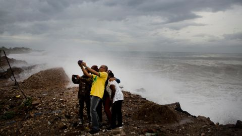 People near Kingston, Jamaica, take a photo in front of the rough surf produced by Hurricane Matthew on October 3.
