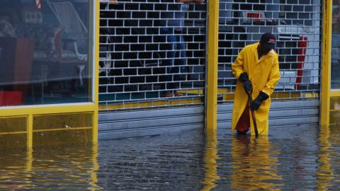 A worker clears a sewer on a flooded street in Santo Domingo.
