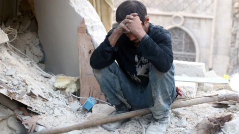 A Syrian man reacts as he sits on the rubble of destroyed buildings following a government forces air strike on the rebel-held neighbourhood of Bustan al-Basha in the northern city of Aleppo, on October 4, 2016. Assad's forces advanced on rebels during intense street fighting in the opposition-held east of Aleppo city, which Russia has been accused of bombing indiscriminately including targeting its hospitals. / AFP PHOTO / THAER MOHAMMEDTHAER MOHAMMED/AFP/Getty Images