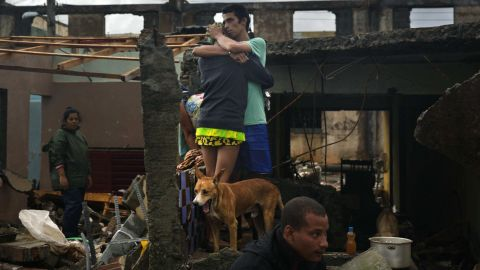 People embrace at their damaged home in Baracoa, Cuba. The hurricane rolled across the sparsely populated tip of Cuba, destroying dozens of homes in the country's easternmost city and leaving hundreds of others damaged.
