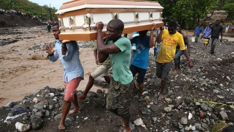 People carry a coffin and try to cross the La Digue river on October 5 after a bridge collapsed in Petit-Goave, Haiti.