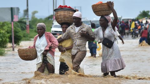 People try to cross the over flowing Rouyonne river in the commune of Leogane, south of Port-au-Prince, October 5.