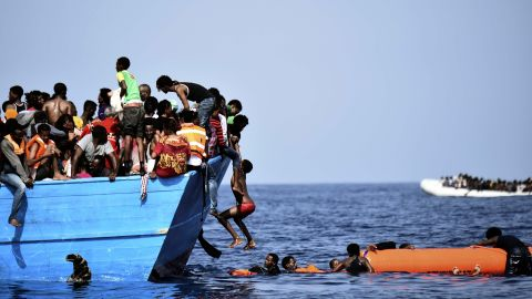 A migrant is lowered into the water during a rescue mission.