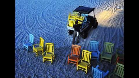 Workers start removing umbrellas and the colorful rocking chairs that line the Cocoa Beach Pier in Cocoa Beach, Florida, on October 5.