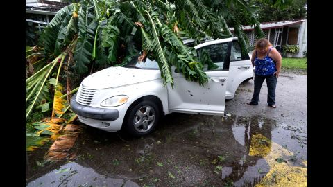 A woman inspects her damaged car under a tree in Fort Pierce, Florida, on October 7.