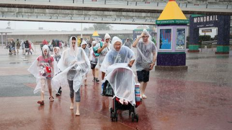 People leave Disney's Magic Kingdom theme park, in heavy rain, after it closed in Orlando, Florida in preparation for the landfall of Hurricane Matthew, on October 6.