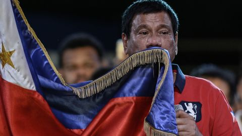 Presidential candidate and Davao Mayor Rodrigo Duterte kisses his national flag as he addresses his supporters during an election campaign rally ahead of the presidential and vice presidential elections in Manila on May 7, 2016.