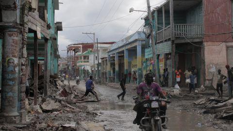 Haitians gather along a flooded street in Haiti on Friday, October 7.