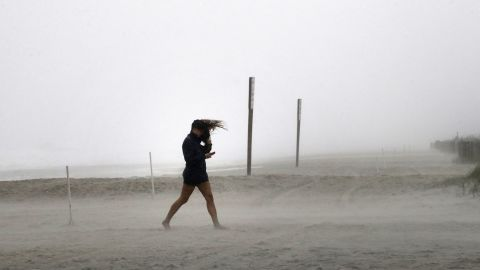 A woman fights the wind in Wrightsville Beach, North Carolina, on October 8.