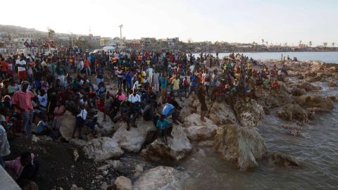 """Residents of Jeremie wait on the shore October 8 as a boat with water and food from the """"Mission of Hope"""" charity arrives. Jeremie appears to be the epicenter of Haiti's growing humanitarian crisis in the wake of the storm."""