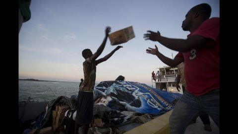 """People unload food and water from a """"Mission of Hope"""" charity boat Saturday after Hurricane Matthew swept through Jeremie."""