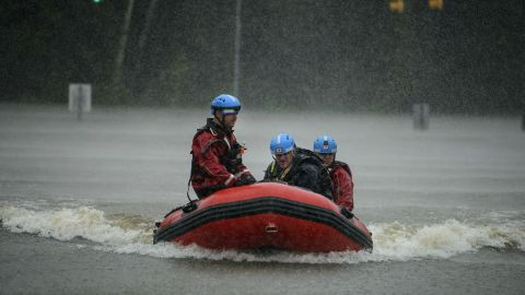 A water rescue team heads to shore at the onramp of MLK Freeway after rescuing Derrick Williams from the flood waters on Robeson Street on Saturday, Oct. 8, 2016, in Fayetteville, N.C.  A fast-weakening Hurricane Matthew continued its march along the Atlantic coast Saturday, lashing two of the South's most historic cities and some of its most popular resort islands, flattening trees, swamping streets and knocking out power to hundreds of thousands.