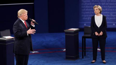 Clinton looks on as Trump speaks.