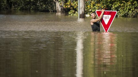 A man clings to a road sign after trying to swim out to help a stranded truck driver in Hope Mills, North Carolina, on October 9. Both were rescued.