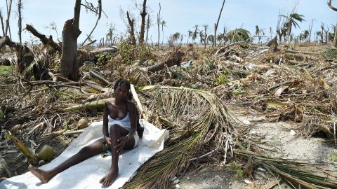 A woman sits in debris where her house once stood in Les Cayes on October 10.