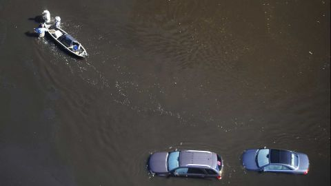 People wade through floodwaters with a boat in Nichols, South Carolina, on Monday, October 10. Hurricane Matthew caused flooding and damage in the Southeast -- from Florida to North Carolina -- after slamming Haiti and other countries in the Caribbean.