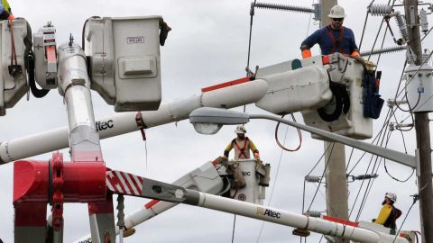 Workers repair downed power lines in Daytona Beach, Florida, on October 10.