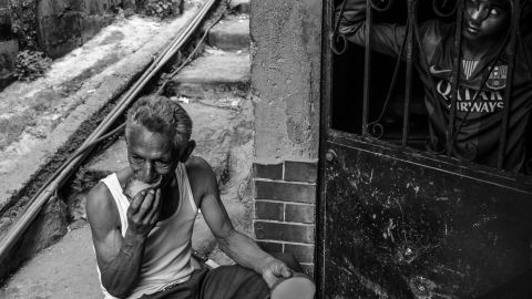 A man eats a mango for lunch in front of his shack in Petare, the largest slum in Caracas.