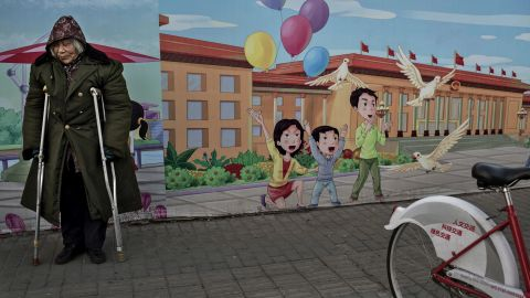 BEIJING, CHINA - DECEMBER 1: A disabled Chinese pensioner stands in the street next to a propaganda billboard showing a cartoon scene depicting the Great Hall of the People, in the street on December 1, 2014 in Beijing, China. Though China's economy is one of the fastest growing in the world and the standard of living has dramatically risen for millions in recent years, there are still many urban poor in the cities who are often migrants from rural areas. (Photo by Kevin Frayer/Getty Images)