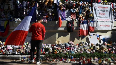 A man wearing a shirt reading in Arabic, 'Long live Tunisia,' and carrying the French national flag looks at candles, toys and flowers placed in commemoration to victims in front of a pavilion at the Promenade des Anglais in Nice, southeastern France, on October 15, 2016, on the occasion of a national tribute to the victims of the July 14 terror attack in which a truck ploughed into crowds celebrating Bastille Day, killing 86 people and injuring more than 400.