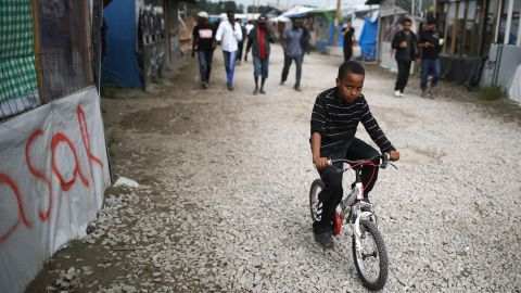 CALAIS, FRANCE - SEPTEMBER 06:  A young boy rides hois bicycle outside the Jungle Books Cafe in the Jungle migrant camp on September 6, 2016 in Calais, France. The drop-in cafe for children is still facing closure and is embroiled in a legal battle with the french authorities. The cafe is run by volunteers and provides safe haven for up to 700 children living in the camp. Children attend language classes, are given free food and the opportunity to charge their mobile telephones so they can contact relatives in their homelands.  Last month a French court rejected a bid by Calais authorities to demolish the Jungle Cafe and other makeshift shops and restaurants but the decision may be facing an appeal.  (Photo by Christopher Furlong/Getty Images)