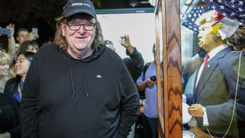 """US filmmaker Michael Moore smiles as he listen to a fortune-telling fairground attraction bearing the likeness of US Republican presidential candidate Donald Trump outside the IFC Theater before attending the debut of a surprise documentary on Trump titled """"TrumpLand"""" in New York on October 18, 2016. / AFP / KENA BETANCUR        (Photo credit should read KENA BETANCUR/AFP/Getty Images)"""