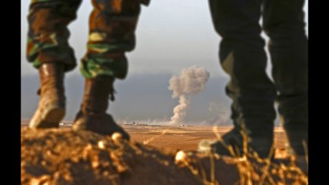 Peshmerga fighters look over a village during an assault near Bashiqa on Thursday, October 20.