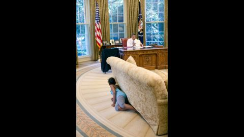 """Sasha Obama hides behind an Oval Office sofa as she sneaks up on her father on August 5, 2009. Sasha was 7 when her father took office. Malia was 10. <a href=""""http://www.cnn.com/2012/09/05/politics/gallery/sasha-and-malia-2008-present/index.html"""" target=""""_blank"""">See more pictures of Malia and Sasha Obama since their father was elected President</a>"""