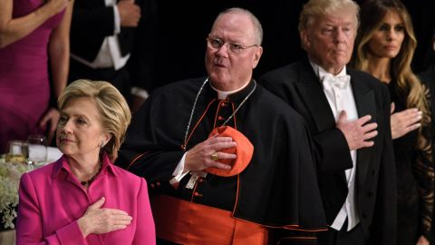 From left Democratic presidential nominee Hillary Clinton, Timothy Cardinal Dolan, Archbishop of New York, Republican presidential nominee Donald Trump and Melania Trump listen to the National Anthem during the Alfred E. Smith Memorial Foundation Dinner at Waldorf Astoria October 20, 2016 in New York, New York.