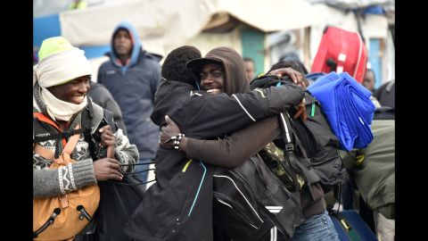 """Residents of the camp hug before departing the """"Jungle"""" on October 24."""