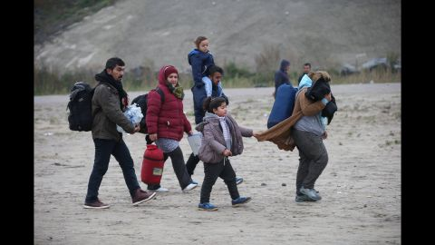 Men, women and children leave the camp during the first day of the planned eviction on October 24.