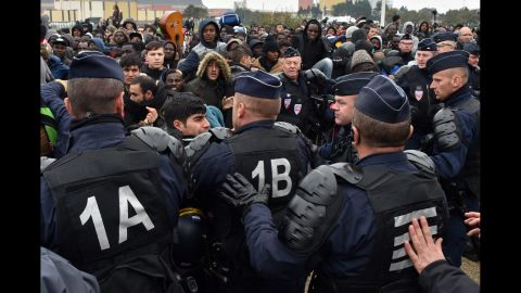 Police try to maintain order as migrants waiting to be processed wait in crowded lines on October 24.
