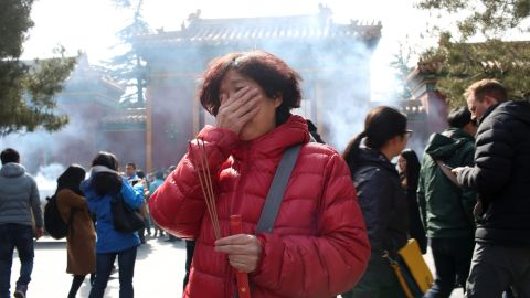BEIJING, CHINA - MARCH 08: (CHINA OUT) A relative of the MH370 victims cries as she burns incense to pray for the missing person in Malaysia Airlines Flight MH370 accident on the two-year anniversary at Yonghe Palace on March 8, 2016 in Beijing, China. Malaysia Airlines Flight MH370 which flew from Kuala Lumpur to Beijing, and which carried 239 passengers mysteriously disappeared on March 8,  2014. The Premier Najib Razak of Malaysia declared on August 6, 2015 that flight MH370 met a tragic end in the Indian Ocean after partial wreckage was found on July 29 on Reunion Island.  (Photo by VCG/VCG via Getty Images)