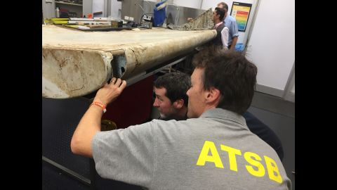 Staff members with the Australian Transport Safety Bureau examine a piece of aircraft debris at their laboratory in Canberra, Australia, on July 20. The flap was found in June by residents on Pemba Island off the coast of Tanzania, and officials had said it was highly likely to have come from Flight 370. Experts at the Australian Transport Safety Bureau, which is heading up the search for the plane, confirmed that the part was indeed from the missing aircraft.