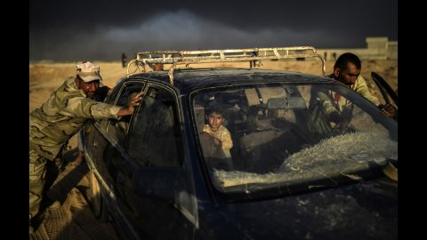 An Iraqi forces member helps a man push a car as they arrive at a refugee camp in Qayyara on October 22.
