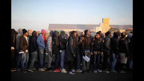 Sudanese migrants wait in line to board buses that will take them to relocation centers across France.