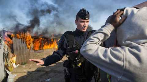 """French authorities stand guard after migrants set fire to a shelter during the dismantling of the Calais """"Jungle"""" camp on October 25."""