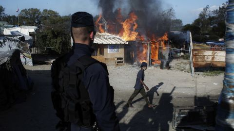 A man passes a camp structure on fire on October 25.