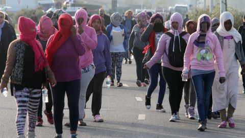 Women arrive at a meeting point determined by authorities managing the evacuation of the camp.