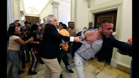 An opposition deputy struggles while pro-government supporters force their way to the National Assembly during an extraordinary session called by opposition leaders in Caracas on October 23. The National Assembly has voted to ask Maduro to appear for questioning next week so it can determine whether to recommend he be removed from office by the nation's Supreme Court.